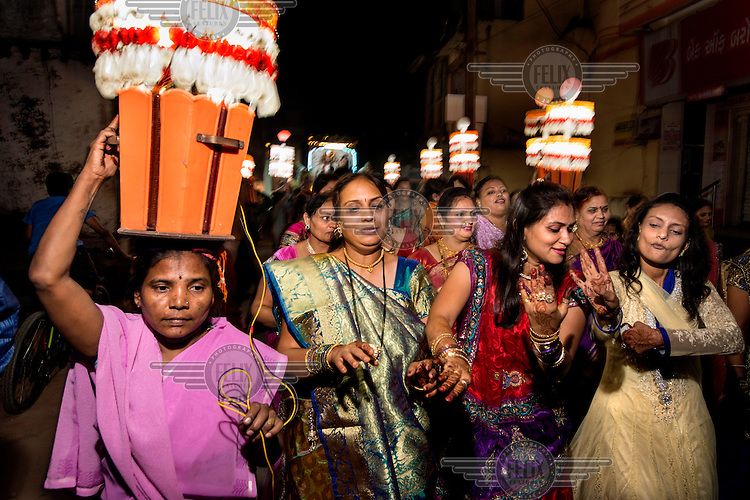 The family and friends of the groom make their way to his marriage ceremony in a noisy procession through the streets of Navsari.