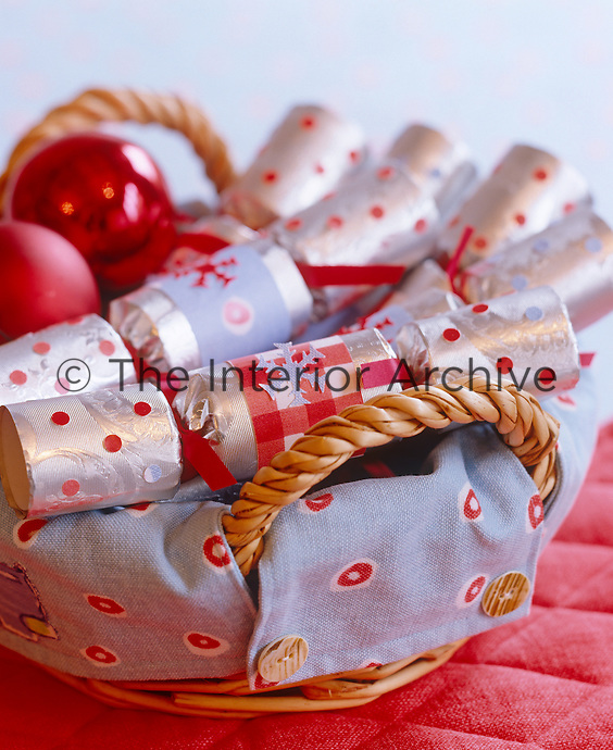 Customised Christmas crackers are stored in a wicker basket lined with fabric