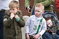 St Patricks Day parade High Street Digbeth .Two young boys with a further one asleep in pushchair watching parade