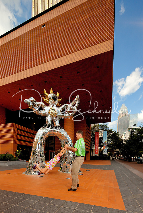 A father and daughter play near the Firebird statue outside the Bechtler Museum of Art in downtown Charlotte, NC.