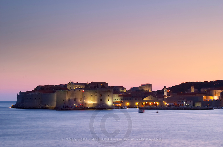 View over the Old Town in the evening after sunset, the city lights glimmering, the sky deep blue and orange pink. View of the Saint John Fort and the old harbour, deep blue sea from the luxury Excelsior Hotel and Spa restaurant terrace Dubrovnik, old city. Dalmatian Coast, Croatia, Europe.