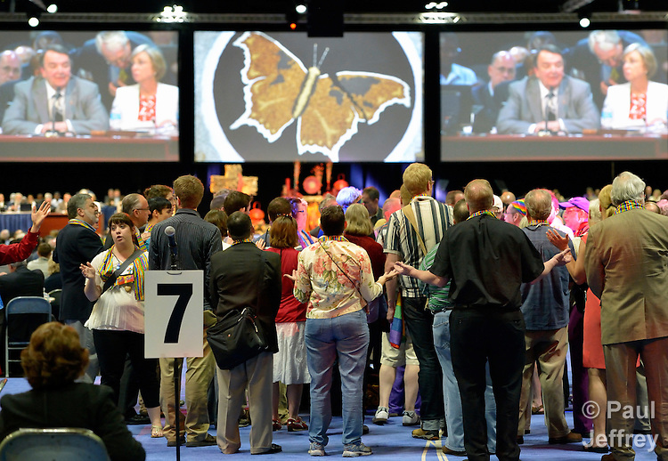 Dozens of demonstrators demanding a more inclusive church took over the floor of a May 3 session of the 2012 United Methodist General Conference in Tampa, Florida. They held communion around the center table and sang songs, causing the presiding bishop, Michael J. Coyner (visible on the screens in the background), to suspend the morning session. The demonstrators left at the beginning of the afternoon session after discussion with several women bishops, who publicly told the demonstrators that they felt the pain they had experienced as a result of the conference's actions to continue the denomination's position on homosexuality.