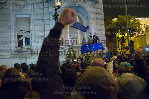 Participant waves an EU flag on the government party headquarters as they protest against the planned Internet tax in Budapest, Hungary on October 26, 2014. ATTILA VOLGYI
