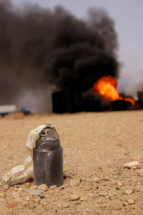 A cluster bomb in the desert by an oil well fire, Southern Iraqi oil field. Unexploded cluster bombs litter the area around the burning oil wells in Iraq's Rumaila Oil Field in Southern Iraq. The wells were set on fire with explosives by retreating Iraqi troops when the US and UK invasion began. The cluster bombs were dropped by US forces to clear the oil well area. A number of them do not explode and this unexploded ordnance is another hazard faced by the experts who have to put the fires out and restore the well heads. The Rumaila field is one of Iraq's biggest oil fields with five billion barrels in reserve. Many of the wells are 10,000 feet deep and produce huge volumes of oil and gas under tremendous pressure, which makes capping them very difficult and dangerous. Rumaila is also spelled Rumeilah.