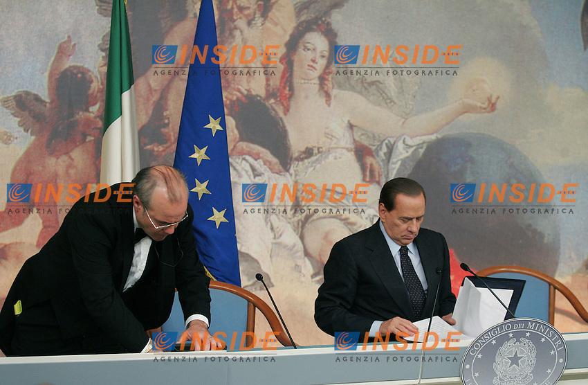 Il Presidente del Consiglio Silvio Berlusconi, a sinistra un commesso sistema le sedie per la successiva conferenza stampa...Conferenza Stampa al termine del Consiglio dei Ministri - Piano Nazionale per il Sud...Roma, 26 Novembre 2010...Photo  Serena Cremaschi Insidefoto..........