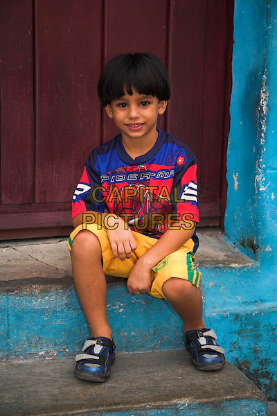 Young boy sitting on a doorstep in front of his home, Camaguey, Camaguey Province, Cuba