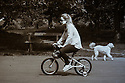 London, UK. 28.05.2016. An adult woman rides her small daughter's bicycle in Regent's Park. Photograph © Jane Hobson.