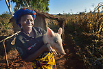 A woman holds a pig in Kaluhoro, Malawi. With support from the Ekwendeni Hospital AIDS Program, she and other villagers participate in a Building Sustainable Livelihoods program, working together to earn and save money, raise more nutritious food, and receive vocational training.