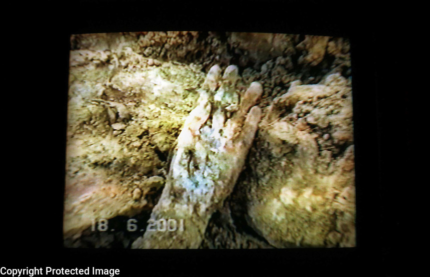 SERBIA. Belgrade. 11 July 2001..A scene from a police video of the exhumation of a mass grave at Batajnica, 15 Kilometres North of Belgrade, shows the hand of one the bodies exhumed. It is suspected that these bodies came from the massacre at Suva Reka, Kosovo, on March 28th 1999..