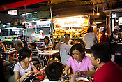 A tourist takes a picture while a family gathers to eat at a Chinese Hawker stall in Gurney Drive, Georgetown in Penang, Malaysia. Photo: Sanjit Das/Panos