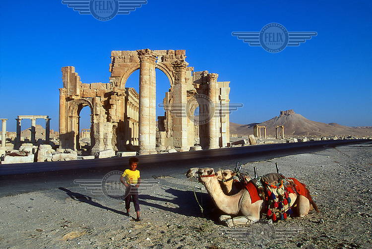 A boy walks past a couple of camels with a view of the ancient ruins of Palmyra (or Tadmor in Arabic) behind. The site dates back to the Neolithic period and was first mentioned in the second millennium BC as a caravan stop. It later came under the Seleucid Empire and then under the Roman Empire.<br /> In May 2015 Islamic State (IS) forces fighting the Syrian government of President Assad took control of the modern settlement of Tadmur and the historic site. There are fears that the priceless treasures could fall victim to IS's iconoclastic destruction that has seen museums and ancient sites across Syria and Iraq destroyed.
