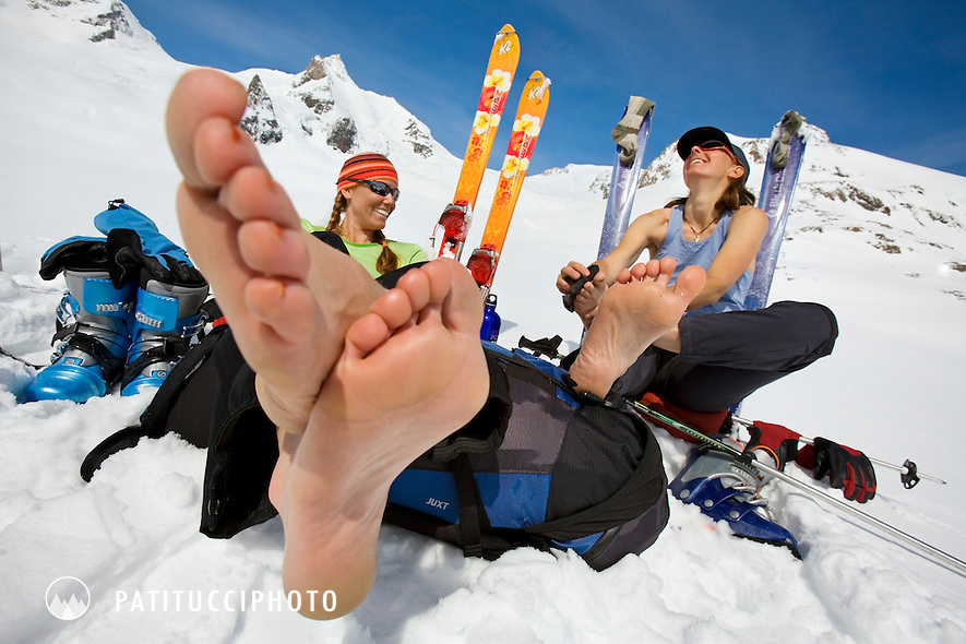 Amy Rasic and Janine Patitucci taking a break from skiing while on the Berner Oberland ski tour. The two have their ski boots off and are letting their feet dry out.