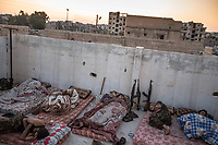 August 2017. Raqqa, Syria.<br /> Members of the MFS sleep in the early hours of the morning on the roof of their nocter (an abandoned house which is now being used as a base) on the front lines.<br /> The MFS (Syriac Military Council) are a group of Assyrian Christians who fight alongside the Syrian Democratic Forces in the fight to topple ISIS.<br /> Photographer: Rick Findler