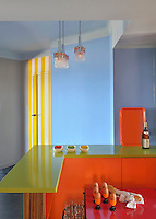 A colourful kitchen with lacquered counter opens onto walls of baby blue and a yellow and white striped painted door