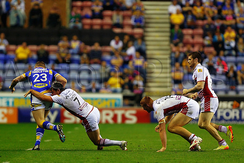 05.09.2014.  Wigan, England.  Super League Rugby. Wigan Warriors versus Leeds Rhinos. Matty Smith of Wigan Warriors tackles Brad Singleton of Leeds Rhinos as he tries to break free
