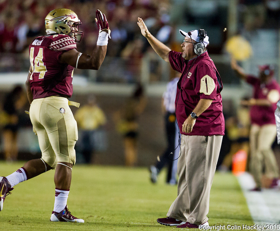 TALLAHASSEE, FLA. 9/5/15-Florida State University linebackers coach Bill Miller, right celebrates with DeMarcus Walker after a play against Texas State at Doak Campbell Stadium in Tallahassee.<br /> <br /> COLIN HACKLEY PHOTO