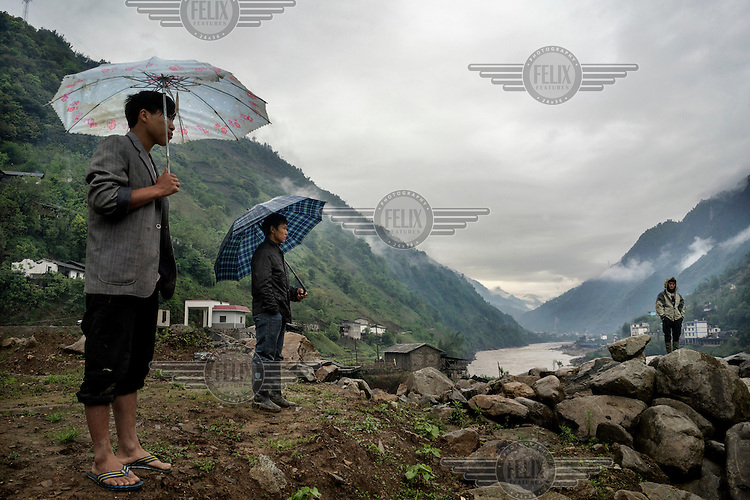 Villagers, sheltering from rain beneath umbrellas, look across the Nujiang River at a landslide that blocked the main road for two days.