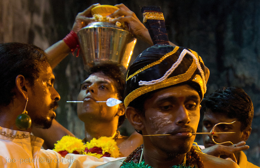 men trance with  Shivas fork-shaped spear thrilled through his cheeks while Thaipusam ceremonies inside Batu Caves, Kuala Lumpur, Malaysia, 2012. Thaipusam ceremonies, celebrated by tamile Hindu community in Malaysia, take place  in Sanctuary of Batu Caves at the border of Kuala Lumpur, each year around end of January or beginning of February, according to Hindu moon calendar. The event is paying hommage to Lord Murugan, a spirit or god created by Shiva to lead the army of gods against the army of evil demons, finally defeating the evil spirits. There are many ways to present offerings or sacrifices for this major religious event. Devotees mortify their bodies by carrying heavy kavaris with spears fixed in their skin or fruits, flowers and little post with holy milk fixed with hooks in their skin, ascending the stairways to the sanctuary in trance, `followed by assistant  taking care and musicians playing loud and fast rhythmic trance music.  Many families shave their head in a ritual before ascending the stairways, as part of rituals to obtain salvation for their ancestors.