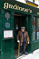Elderly local Irishman with walking stick leaving Grainne's Bar in Mill Street, Timoleague, West Cork, Ireland