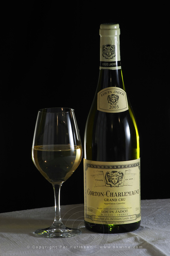 A bottle of Maison Louis Jadot Bourgogne Corton Charlemagne Grand Cru 2003 white burgundy wine and a glass of white wine standing on a table top with a white cloth. Backlit backlight back light lit. Black background, Maison Louis Jadot, Beaune Côte Cote d Or Bourgogne Burgundy Burgundian France French Europe European