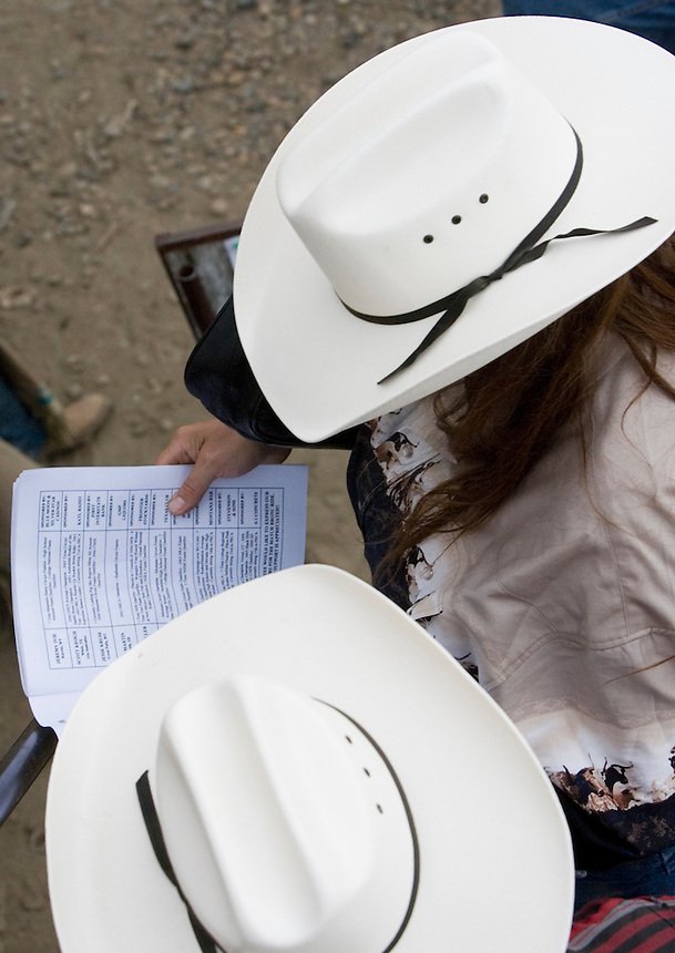 A pair of spectators look over the Miles City Bucking Horse Sale program at the Eastern Montana Fairgrounds in Miles City Montana Sat., May 19, 2007. Saddle broncs and bareback broncs are auctioned off after they are bucked.