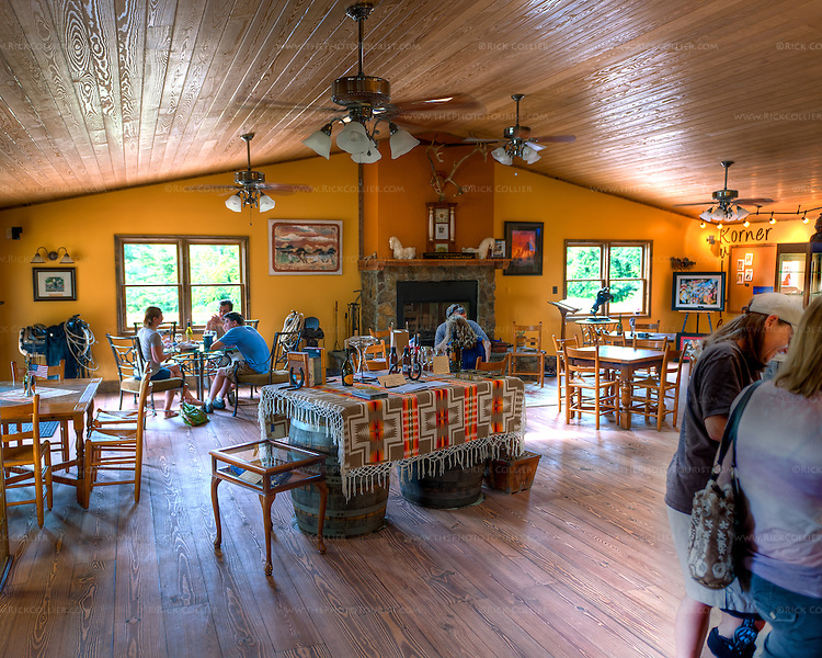 The tasting room at Desert Rose Ranch and Winery has numerous tables, scattered around a stonework fireplace. (HDR image)