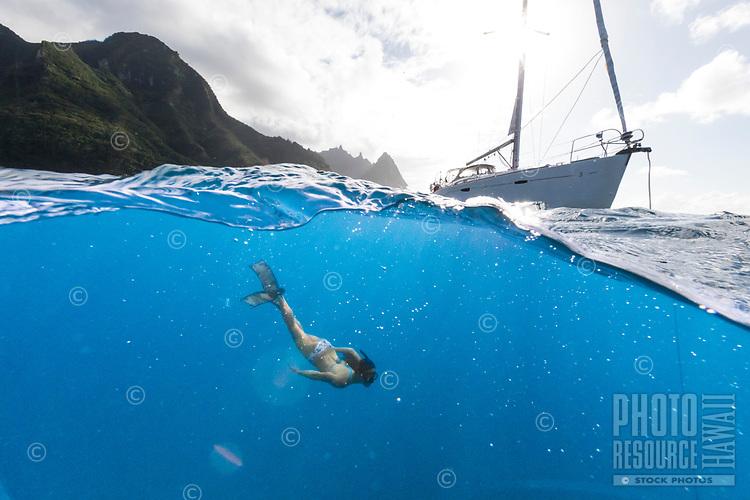 A woman free dives off an anchored sailboat on the Na Pali Coast of Kauai