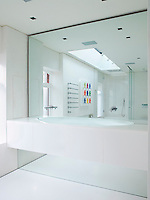 A wall to wall mirror above the long basin in the minimal bathroom makes the already spacious room appear even larger