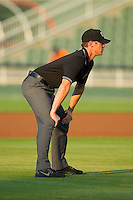 Umpire Clayton Hamm handles the calls on the bases during the South Atlantic League game between the Hickory Crawdads and the Kannapolis Intimidators at CMC-Northeast Stadium on July 26, 2013 in Kannapolis, North Carolina.  The Intimidators defeated the Crawdads 2-1.  (Brian Westerholt/Four Seam Images)