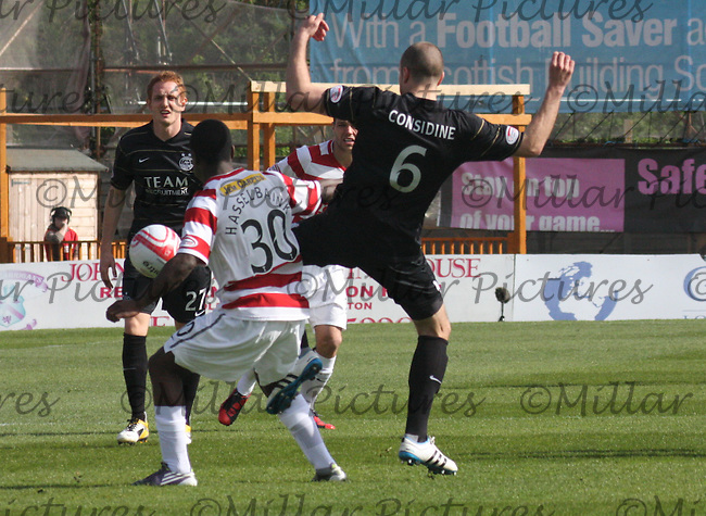 Nigel Hasselbank shields the ball from Andrew Considine as Robert Milsom looks on
