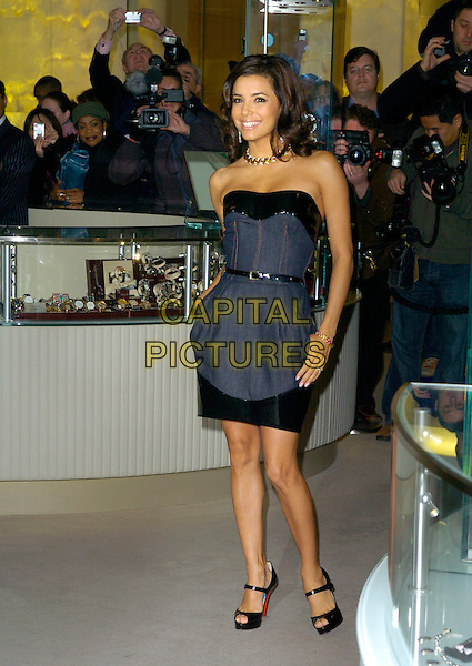 EVA LONGORIA.opens Harrods Winter Sale, Knightsbridge,.London, England, 28th December 2006..full length mini dress by Dolce and Gabbana strapless Christian Louboutin ankle strap shoes open toe black belt patent shiny hands in pockets.CAP/CAN .©Can Nguyen/Capital Pictures