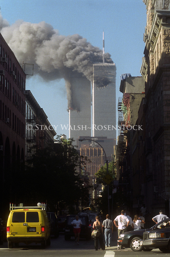 (010911-SWR2-4.jpg) - New York, NY -- 11 Sept 2001 - WORLD TRADE CENTER COLLAPSES AFTER TERRORISTS FLY HIJACKED PLANES INTO TWIN TOWERS - Smoke and flames rise from the Twin Towers in lower Manhattan ater one American Airlines and one United Airlines commercial airplains plane hijacked by terrporists were flown directly into each tower. The first plane hit at approximate 8:42 am Eastern Standard Time. Officials estimate somewhere between 20,000 and 50,000 people were in each tower at the time of the attack. Soon afterwards both towers collapsed. The city was shut down a and Mayor Giuliani moved to aa secure location. All bridges and tunnels were closed. Subeay service ceased and primary elections were cancelled.