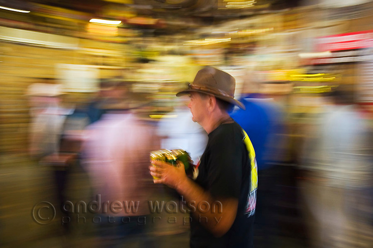 A drinker carries beers from the bar at the Birdsville Hotel during the annual Birdsville races.  Dating back to 1884 the historic pub is one of the most famous drinking holes in outback Australia and sees thousands of visitors during the September horse racing carnival. Birdsville, Queensland, AUSTRALIA.