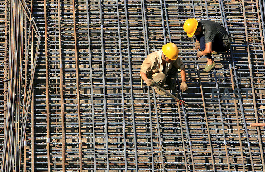 Workers attach steel rods together to build the foundations of China World Tower 3 on the building's construction site in Beijing, China, Monday, August 21,  2006. Photo by Servais Mont/Pictobank