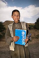 A schoolboy holding a UNICEF writing pad.