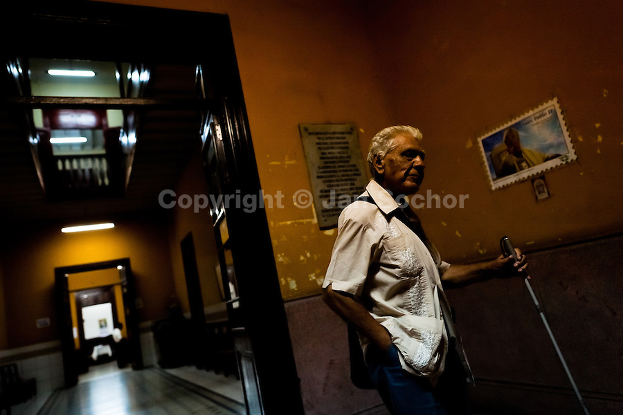 A blind man, using a white cane, finds his way in the foyer of Unión Nacional de Ciegos del Perú, a social club for the visually impaired in Lima, Peru, 4 April 2013. Unión Nacional de Ciegos del Perú, one of the first societies for disabled in Latin America, was established in 1931 to provide a daily service for blind and partially sighted people from the capital city. The range of activities includes reading books in a large Braille library, playing chess or using a computer adapted for visually impaired individuals. As the majority of the blind does not have a regular job, the UNCP club offers them an opportunity to learn and lately, to provide massages to the club visitors and thus generate some income.