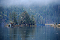 Clouds obscure the mountains surrounding Landlock Bay, Port Fidalgo in Prince William Sound, Alaska on a rainy spring evening in early May.
