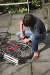 Model released image of boy pumping air into his bike tyre, Suffolk, England,UK