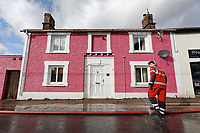 Pictured: A fireman handles a hose.<br /> Re: Cleanup after storm Dennis in Crickhowell, Wales, UK.