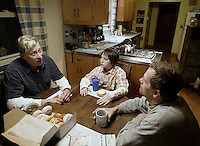 10-year-old Michael O'Reilly-Birtcher, center, eats breakfast with his adoptive parents Thom O'Reilly, left, and Harold Birtcher in their home Thursday, Feb. 16, 2006, in Upper Arlington, Ohio. Because same-sex partners are barred from joint adoption in Ohio, O?Reilly and Birtcher, who have been together for 25 years, went to Oregon three years ago to jointly adopt Michael. A bill introduced in the Ohio Legislature this month would bar all gays and lesbians from adoptions and foster care.<br />