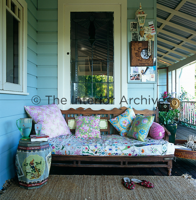 An antique sofa scattered with colourful cushions has been placed in a sheltered corner of the spacious verandah which surrounds the house