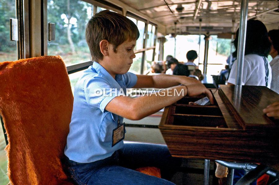 Criança trabalhando como cobrador em ônibus em Foz de Iguaçú. Paraná. 1984. Foto de Juca Martins..