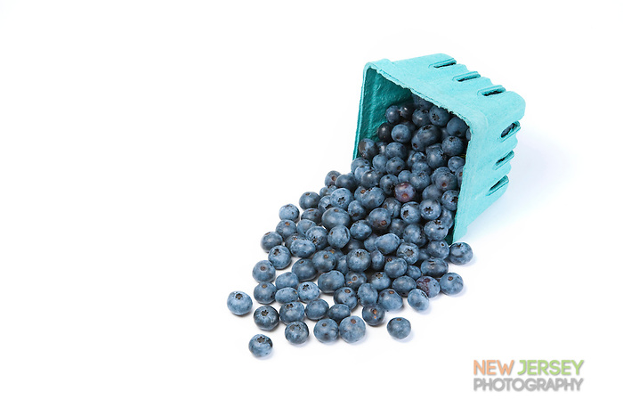 Ripe blueberries, spilling out of a pint sized box