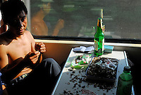 A passenger eats sun-flower seeds on a train on the way from Lanzhou to Xining in China. The area has a large muslim population..09 Jul 2006