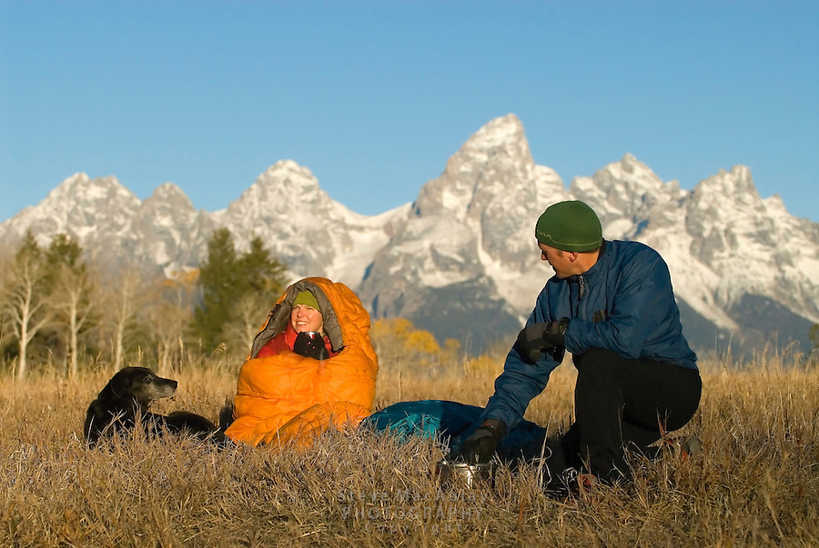 Young woman wrapped up in orange sleeping bag, holding coffee mug, while male camper works with camp stove and watches dog. at sunrise at campsite,Fall, Grand Teton National Park, Wyoming