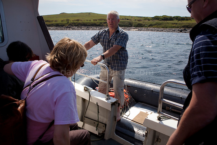 Ferry operator Declan Bates, welcoming passengers into an inflatable boat to coplete the journey o the Saltee Islands, off the coast of Co. Wexford, Ireland.