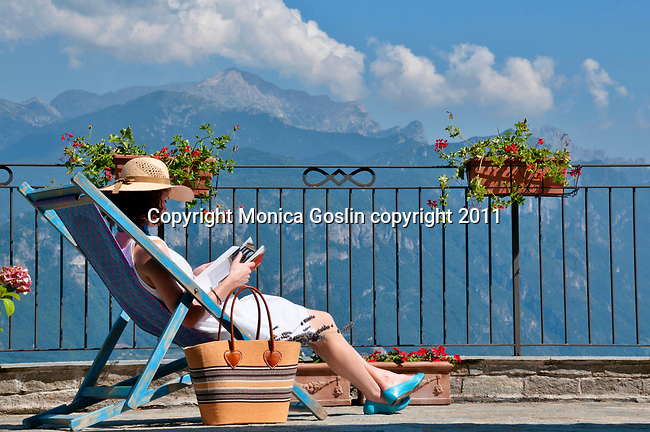 A girl in a white dress and wearing a straw hat reads a book with of Lake Como, Italy in the background