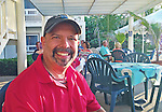 9 July 2013: SCUBA Instructor, photographer, and Architect Ed Wolfstein smiles on the oceanside deck at Cobalt Coast Resort, in West Bay, Grand Cayman Island. Located in the British West Indies in the  Caribbean, the Cayman Islands are renowned for excellent scuba diving, snorkeling, beaches and banking.  Mandatory Credit: Ed Wolfstein Photo