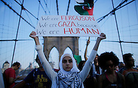 New York City, NY. 20 August 2014. A woman holds a banner as he takes part during a Pro-palestine Rally across de Brooklyn Bridge in Manhattan.  Photo by Kena Betancur/VIEWpress