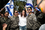 "© Licensed to London News Pictures . 03/06/2016 . Tel Aviv , Israel . MIRI REGEV (c) , Israeli Minister of Culture and Sport , posing with soldiers . Over 100,000 people attend the gay pride parade in Tel Aviv , reported to be the largest such event in the Middle East and Asia . The Israeli government has been accused of using the event as "" pinkwashing "" , marketing the event in order to deflect accusations of poor human rights behaviour . Photo credit: Joel Goodman/LNP"
